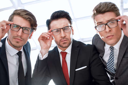 close up.three attentive businessmen looking at the camera