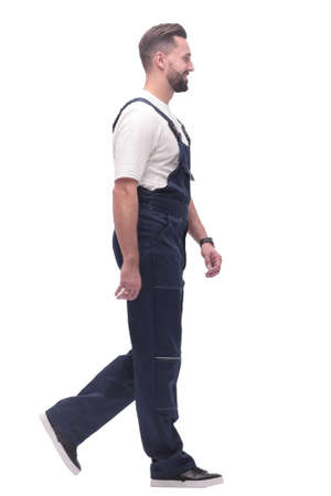 side view. smiling man in overalls confidently striding forward