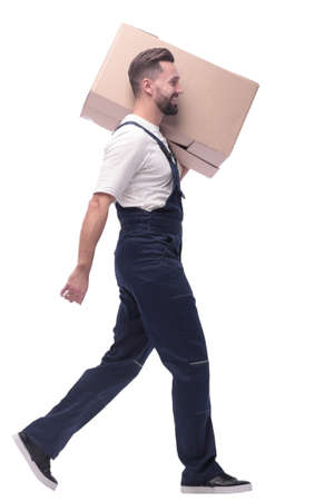 side view. a man in overalls carries a large cardboard box
