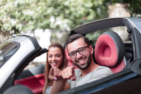 happy couple sitting inside a convertible and pointing at you