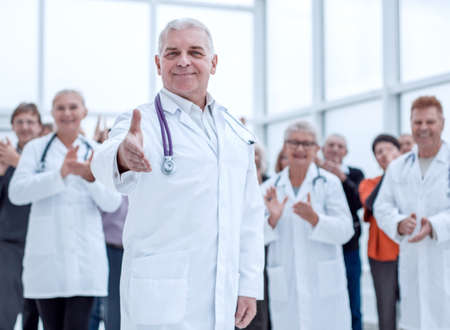 Group of elderly and experienced doctors greeting on camera Stock Photo
