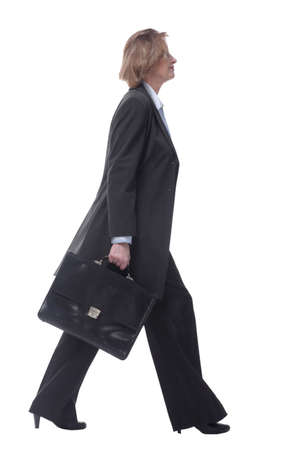 Smiling mature businesswoman walking to side with briefcase