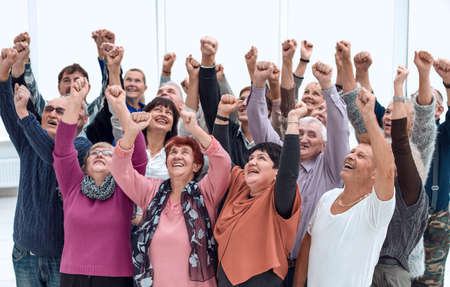 a group of elderly people raised their hands up