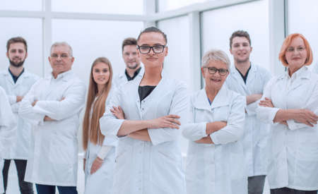 young researcher standing ahead of her senior colleagues.