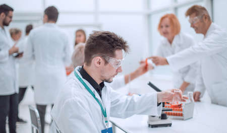 young scientist looking at a test tube with test results.