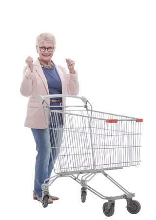 in full growth. a very happy old woman with a shopping cart