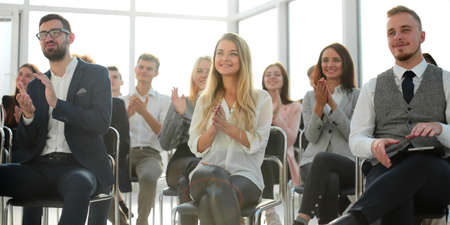 group of listeners applaud from the conference room