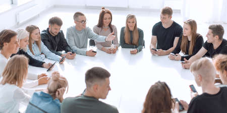 group of young people with smartphones sitting at a round table
