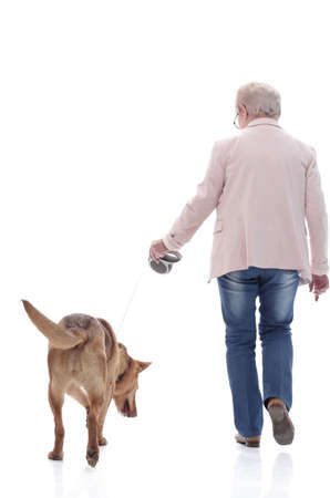 side view . senior lady and her dog walking together