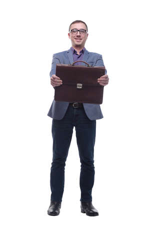 Young businessman wearing jeans ans glasses holding briefcase in front of him