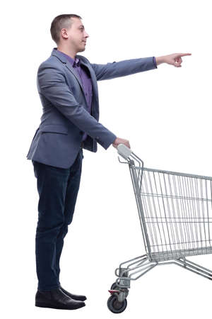 Full length view of handsome young man standing with shopping trolley and looking at camera