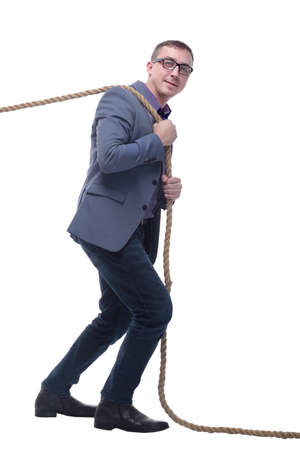 Side view of businessman in suit pulling a rope while standing against white background