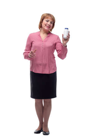 Middle aged woman holding glass bottle with pills, smiling and standing isolated on white background