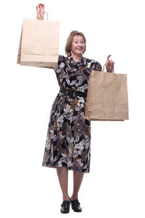 Mature woman holding bags smiling and looking at camera