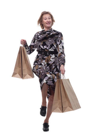 Caucasian senior woman walking with shopping bags smiling at viewer