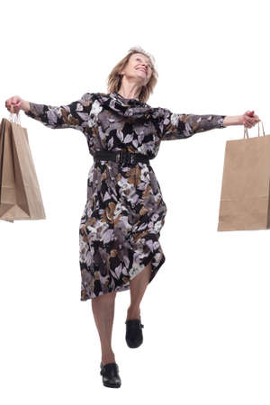 Happy middle aged woman holding shopping bags isolated on white background and dancing