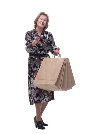 Senior woman holding shopping bags on sales very happy pointing with hand and finger to the camera