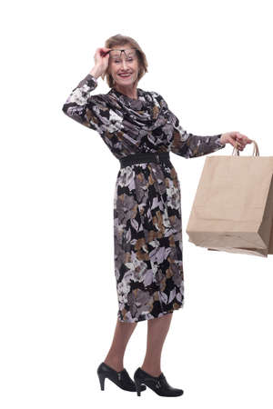 Senior woman addicted to shopping, holding up a handful of bags. Standard-Bild - 167073309