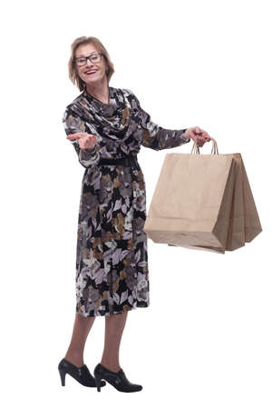 Senior woman addicted to shopping, holding up a handful of bags. Standard-Bild