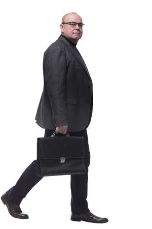side view. a business man with a leather briefcase striding forward.