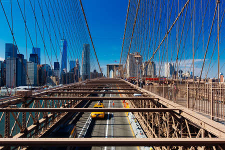 Spring April 2015 Brooklyn Bridge Traffic with yellow cab and people, New York United States