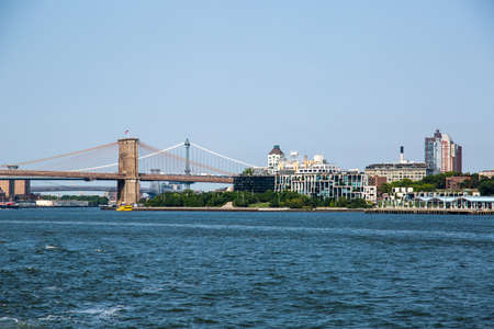 New York City  USA - JUL 14 2018: Brooklyn Bridge view from Governors Island ferry on a clear afternoon