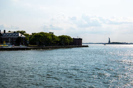 New York City  USA - JUL 14 2018: Governors Island and Statue of Liberty view from ferry on a clear afternoon Editorial