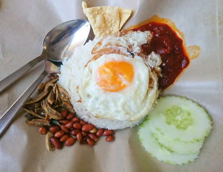 Nasi lemak served with sambal, half fried egg, ikan bilis, fried red peanut and papadom