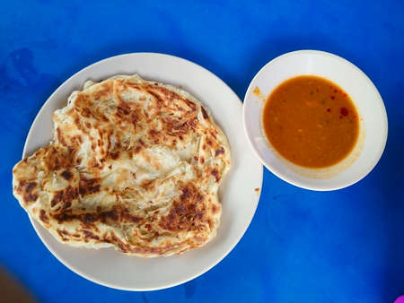 Roti canai served with curry on plate. Top view. Malaysian popular breakfast meal Stock Photo