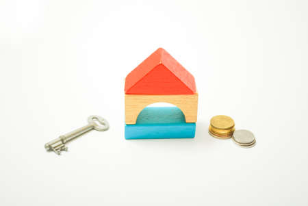 Conceptual image of miniature home icon made from wood bricks, key and coin on isolated white background