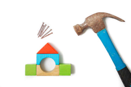 Construction conceptual image with house miniature from blocks, nails and hammer. Isolated white background