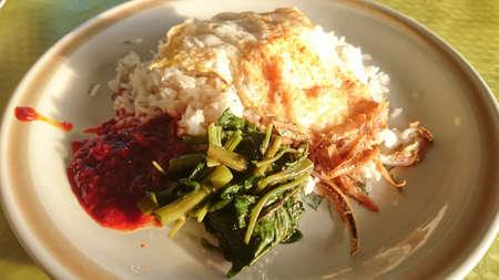 Nasi lemak a Malaysia popular food. Serve with sambal, fried egg, kangkung and ikan bilis. Top view