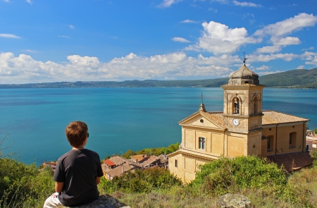A young man is looking a landscape with the Main Church of Trevigano Romano, a very nice and little village on the Bracciano Lake, near Rome Standard-Bild