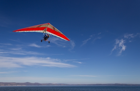 an hang glider flying over Bracciano lak,e, near Rome, italy in a very clear, sunny day