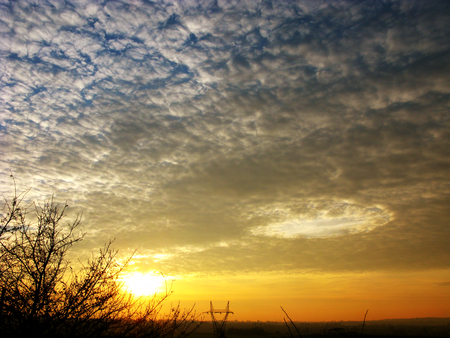 A singular cloud formation in a mackerel sky at sunset photo