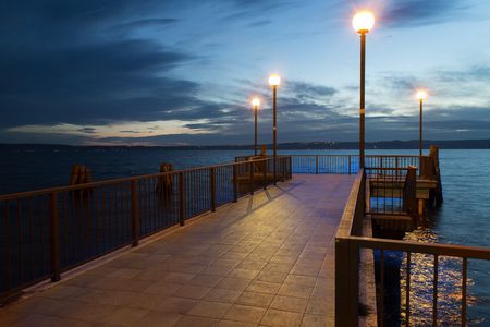 Pier at the dusk, with some lamps lighted photo