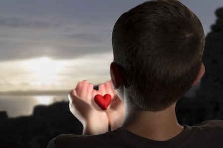 A Young boy holding an hearth in his hands in a sunrise sea landscape. Valentines day composition. photo