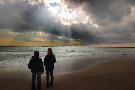 A mother and a teen soon are standing on the beach contemplating a spectacular seascape and sunrays