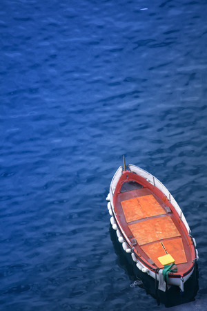 A little boat viewed from an higher point of view in Sorrento bay, a picturesque city near Naples, Italy