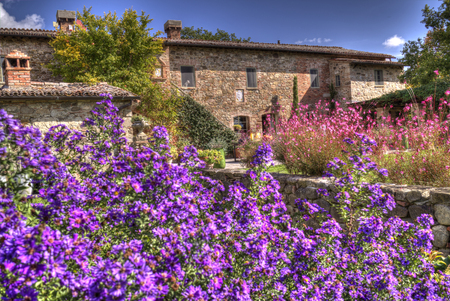 A classical Tuscan country house with flowers and trees in a sunny, brigth day. Standard-Bild