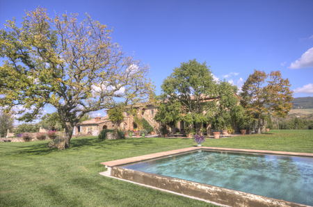 A vintage, country swimming pool in aTuscan estate, in Italy, surrounded by a curated green field  in a sunny, brigth day. Standard-Bild