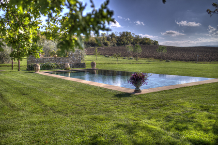 A country swimming pool in aTuscan estate, in Italy, surrounded by a curated green field  in a sunny, brigth day.