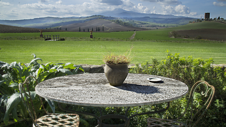 A country round table in classical old style with a marvellous view on tuscan Val d'Orcia landscape Standard-Bild