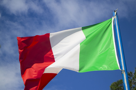 An italian flag waving in the wind in a clear, sunny day