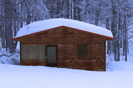A wooden, nice little house covered by snow in a typical winter mountain