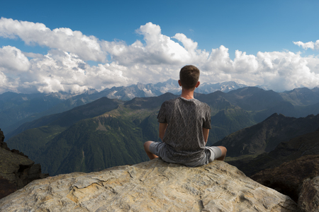 A young boy sitting on a rock on a cliff edge is looking the mountains all around him Standard-Bild