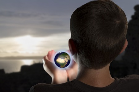 A young man is looking at a little earth in his hands in a evocative, fantasy scenery Standard-Bild