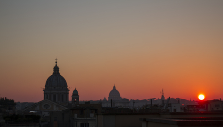 View of Rome cityscape from the roof of so called Pincio in Rome, Italy, at sunset, with typical roman roofs and domes