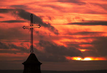Particular image of a cross upon a church during a wonderful, cloudy red sunset Standard-Bild