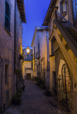 A typical street of little town of Trevignano Romano, on Bracciano lake, near Rome, Italy at the dusk, nicely illuminated by lamps